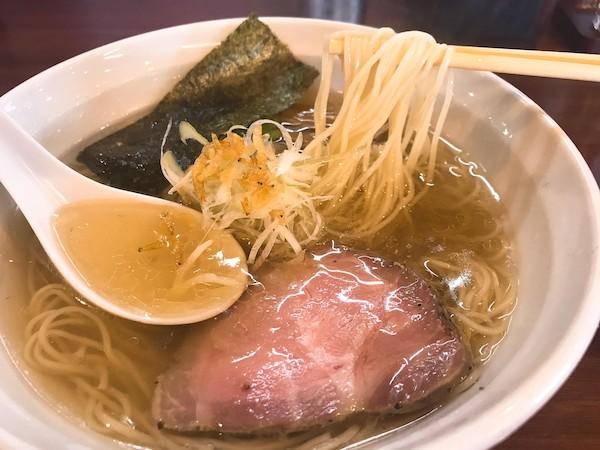 透明度のあるスープの中から細麺を箸で一掴み持ち上げています。