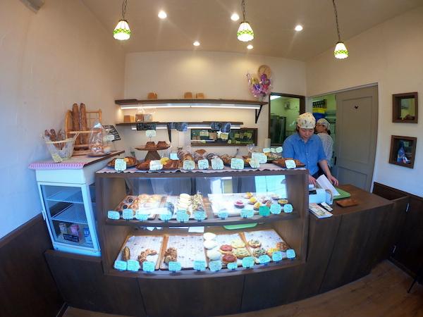 お客さんが4、5人入れるほどのスペースで、正面のショーケース内と上部にパンがたくさん並んでるタカナベーカリーの内観