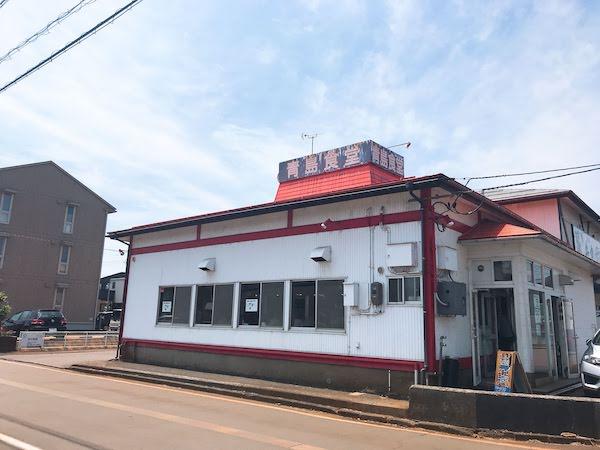 白い外壁に赤い屋根の外観で屋根の上に「青島食堂」と書かれた看板があります。