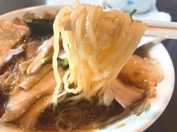 箸でひとつかみされたツルツルの麺。
